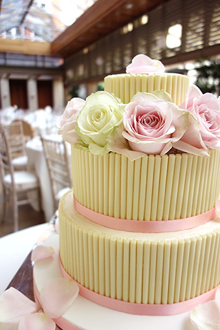 Gluten-free wedding cake. Three tiers of Rich Chocolate Cake. Covered with white chocolate ganache and cigarellos, and dressed with fresh roses. All the ingredients in this wedding cake are gluten free. Roses by Nichlas Vilsmark