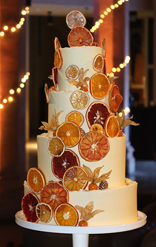A four-tier winter wedding cake. Two tiers of gluten-free lemon cake, and two of orange. Filled and frosted with sweet & sharp organic buttercream, and decorated with dried orange, grapefruit & lemon slices. All ingredients gluten free. Price includes tasting consultation, and delivery & assembly at your London venue