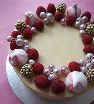 Gluten free Vanilla Cake, filled with raspberry jam and frosted with vanilla buttercream. Decorated with meringue kisses and fresh berries dusted with gold and silver lustre. All ingredients gluten-free. Delivery available in London