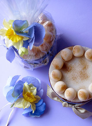 The perfect glutenfree gift for Mother's Day or Easter – a zesty, gluten-free Simnel Cake. Made with organic fruit steamed in apple juice. Topped with organic marzipan: eleven balls represent the apostles, but not Judas. All ingredients gluten free. With blue satin ribbon, gold lamé bow and posy of silk spring flowers. Delivery by post to UK, hand delivery available in London