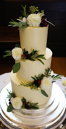Gluten-free, 3-tier White Chocolate and Chocolate & Orange Wedding Cake, covered with white chocolate Swiss meringue buttercream frosting. Decorated with berries and foliage, and organic edible flowers. For a wedding at Stationers' Hall in the City of London